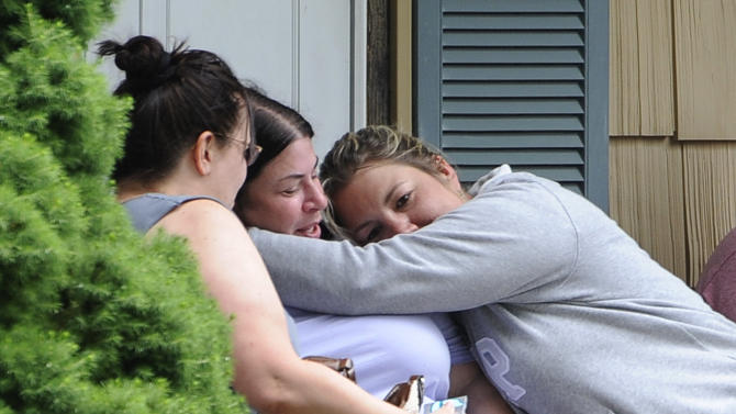 Kerry Gottlieb, center, owner of the home where a small airplane crashed in her backyard that killed the pilot is hugged by friend, Jill Cherveny, right on Tuesday, June 17, 2014, in East Patchogue, N.Y. The plane crashed in between two houses on the tree-lined working-class street, according to Brookhaven Town spokesman Kevin Molloy. The Federal Aviation Administration said the aircraft was a single-engine Lancair Columbia with one person was on board. It was flying from Republic Airport in Farmingdale to MacArthur Airport in Islip, the agency said. (AP Photo/Kathy Kmonicek)