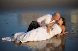 Married couple kissing in the mud after wedding