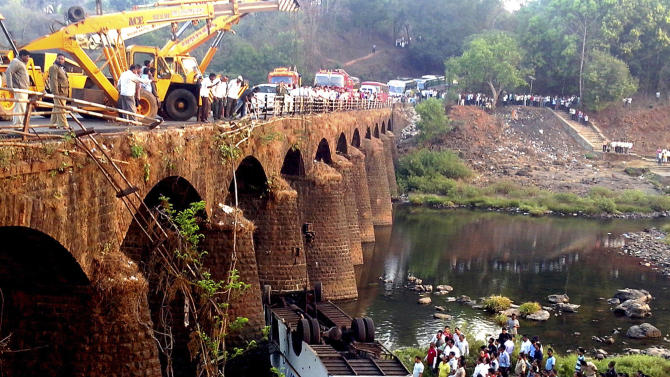 Rescuers and others gather at the site of a bus accident in Ratnagiri district, in the western Indian state of Maharashtra, Tuesday, March 19, 2013. The bus packed with passengers crashed through a guard rail and fell off a bridge in western India early Tuesday, killing at least 37 people and injuring another 15, police said. (AP Photo)