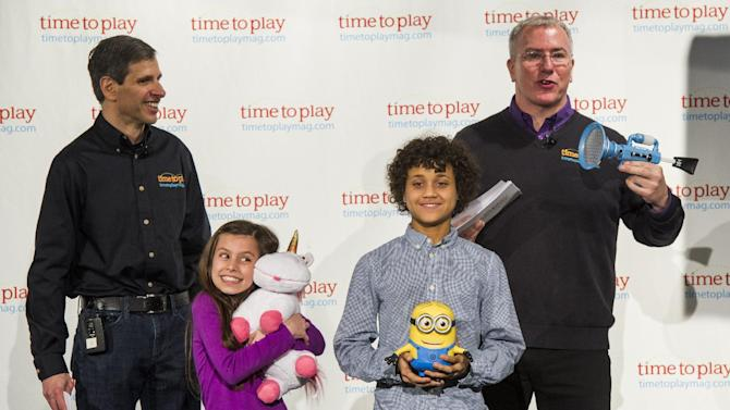 IMAGE DISTRIBUTED FOR TIME TO PLAY - Jim Silver, left, CEO/editor in chief of TimetoPlayMag.com, Chris Byrne, right, content director a.k.a. The Toy Guy, right, and a group of child demonstrators display the Time to Play 2013 Summer Playlist, a roundup of the season's most fun and engaging toys, at the Time to Play Spring Showcase on Tuesday, April 30, 2013 in New York. (Photo by Charles Sykes/Invision for Time to Play/AP Images)