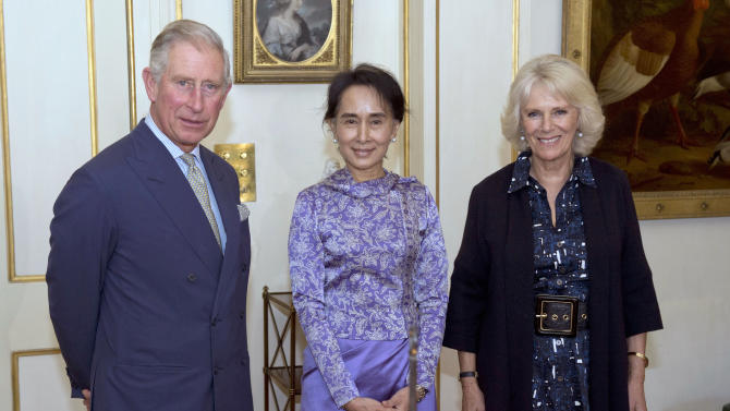 Myanmar opposition leader Aung San Suu Kyi , centre, stands with Britain's Prince Charles Camilla Duchess of Cornwall during a meeting at Clarence House, in London Wednesday Oct. 23, 2013. (AP Photo/Arthur Edwards/Pool)
