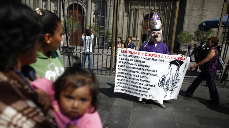 A woman, dressed as a cardinal and wearing a hog mask, holds a banner while yelling slogans against the Catholic clergy outside the Metropolitan Cathedral in Mexico City