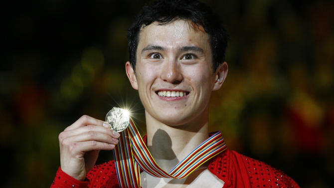 Patrick Chan of Canada, holds his gold medal on the podium of the men's Free skating event at the ISU 2012 World Figure Skating Championships in Nice, southern France, Saturday, March 31, 2012. (AP Photo/ Francois Mori)