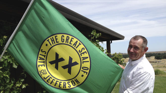 Tom Knorr, chairman of the Measure A campaign in Tehama County, holds a State of Jefferson flag as he poses for photographs at his ranch house in Corning, Calif., Tuesday, May 27, 2014. The idea of forming their own state has been a topic among local secession dreamers for more than a century in California's largely rural, agrarian and politically conservative far northern counties. Residents in two counties, Del Norte and Tehama, will decide June 3, 2014, on an advisory measure that asks each county's board of supervisors to join a wider effort to form a 51st state named Jefferson. (AP Photo/Terry Chea)