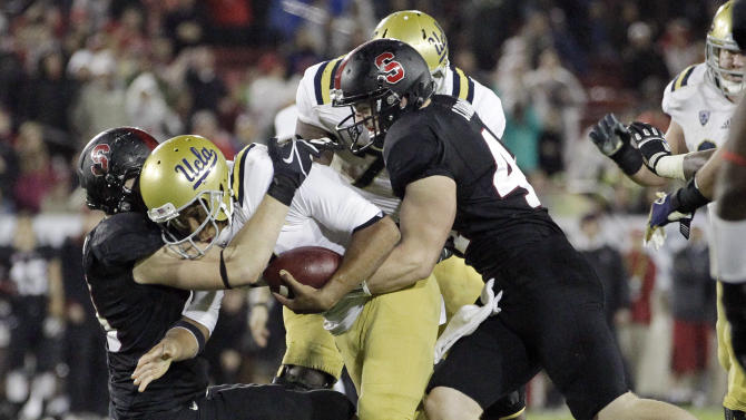 UCLA quarterback Brett Hundley, center, is sacked against Stanford during the second half of the Pac-12 championship NCAA college football game in Stanford, Calif., Friday, Nov. 30, 2012. (AP Photo/Tony Avelar)
