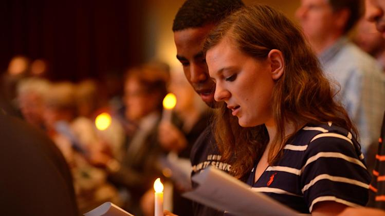 "In this photo provided by the University of Mississippi, Ole Miss freshmen and Ridgeland, Miss., natives Brice Ashford, left, and Lisa Ann Parr hold an electric candle together and sing ""Lift Every Voice and Sing"" at the University of Mississippi's celebration of 50-years of integration in Oxford, Miss., Sunday evening, Sept. 30, 2012. The candle lighting had been scheduled to take place at the Lyceum as a culmination of a ""Walk of Reconciliation and Redemption"", but all of the evening's events were moved to the University's Gertrude Ford Center for the Performing Arts. (AP Photo/University of Mississippi, Robert Jordan)"