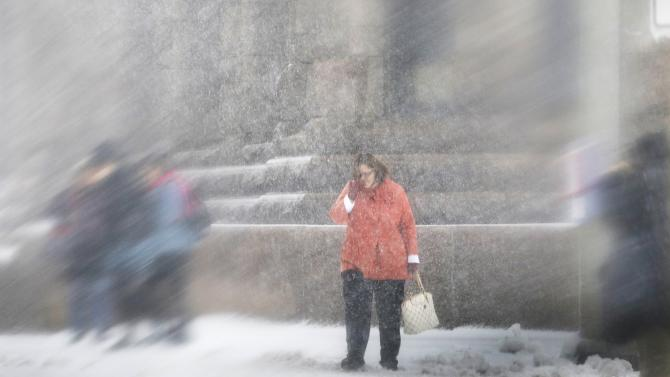 A woman,  seen through a wet windshield, waits to cross a downtown Minneapolis street as a Spring storm hit the Twin Cities and other parts of the state Thursday, April 18, 2013. (AP Photo/Jim Mone)