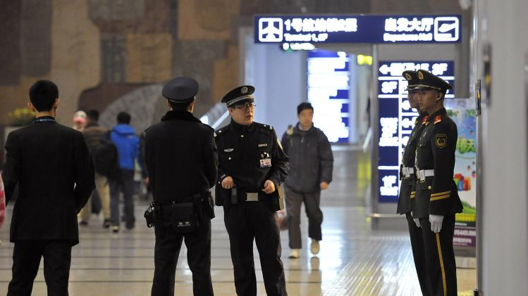Paramilitary policemen stand guard next to policemen at an airport after the disappearance of Malaysia Airlines flight MH370, at an airport in Beijing