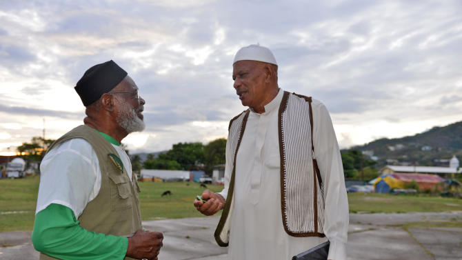In this photo taken May 3, 2013, Yasin Abu Bakr, right, who led a small army that stormed Trinidad & Tobago's parliament in 1990, speaks with a fellow member of his group, Jamaat al Muslimeen, at their compound in Port-of-Spain, Trinidad.  Bakr, never convicted of any charges, presides over a mosque and school complex in the country's capital, and shares time among his four wives, the maximum Islam allows. Bakr said he hasn't decided if he'll testify before the five-member  commission, which is expected to finish collecting testimony by year's end. (AP Photo/David McFadden)
