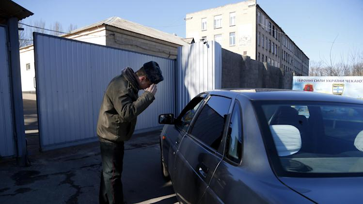 A Ukrainian army officer salutes the driver of a car at the gate of a regional military commissariat during a visit by the Organization for Security and Co-operation in Europe (OSCE) mission in Donetsk, Ukraine, Thursday, March 13, 2014. A potent mix of economic depression, ethnic solidarity and nostalgia for the certainties of the Soviet past have many in eastern Ukraine demanding the right to become part of Russia as well. (AP Photo/Sergei Grits)