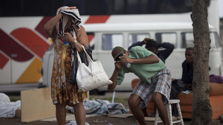 "In this photo taken Nov. 29, 2012, a woman, left, and a man smoke crack in Rio de Janeiro, Brazil. The South American country began experiencing a public health emergency in recent years as demand for crack boomed and open-air ""cracolandias,"" or crack lands, popped up in the sprawling urban centers of Rio and Sao Paulo, with hundreds of users gathering to smoke the drug. The federal government announced in early 2012 that more than $2 billion would be spent to fight the epidemic, with the money spent to train local health care workers, purchase thousands of hospital and shelter beds for emergency treatment, and create transitional centers for recovering users. (AP Photo/Felipe Dana)"
