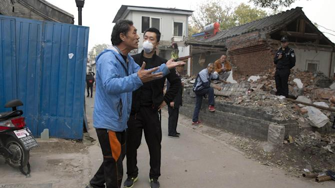 A Chinese resident rants against the forced eviction as Chinese policemen keep watch on residents over a recently demolished house in the Drum and Bell tower district, popular with tourists and marked for redevelopment, in Beijing Friday, Oct. 24, 2014. The Chinese capital has undergone rapid redevelopment over the past decades that has seen former residents pushed outside of the city center in favor of commercial development catering to tourism and retail. (AP Photo/Ng Han Guan)