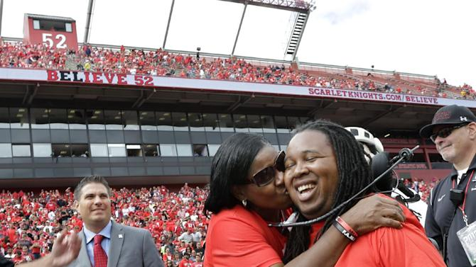 Former Rutgers football player Eric LeGrand is kissed by his mother Karen during ceremony where his jersey No. 52 was retired at halftime of an NCAA college football game against Eastern Michigan in Piscataway,N.J., Saturday, Sept. 14, 2013. LeGrand became paralyzed while making a tackle in an October 2010 game