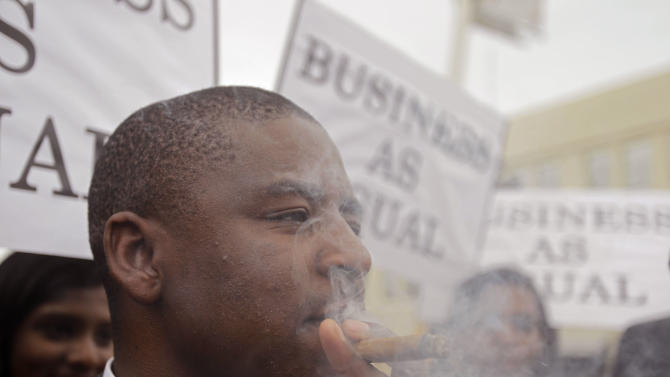 A Green Peace protester smokes a cigar as he and others dress as delegates and  politician, and toast the climate change summit failure with champagne, as it  nears it's end in the city of Durban, South Africa, Saturday, Dec 10, 2011. Some ministers and top climate negotiators left Durban without an agreement Saturday, with time running out and the prospect of an inconclusive end jeopardizing new momentum in the fight against global warming. (AP Photo/Schalk van Zuydam)