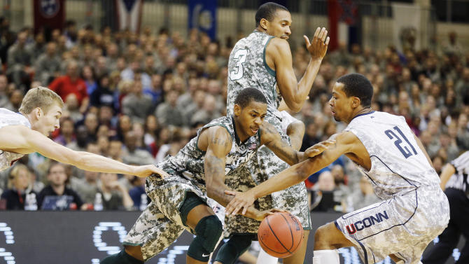 Michigan State guard Keith Appling, center, and Connecticut guard Omar Calhoun (21) vie for the ball during their NCAA men's basketball game on Saturday, Nov. 10, 2012, on the Ramstein U.S. Air Force Base, in Ramstein, Germany.  (AP Photo/Michael Probst)