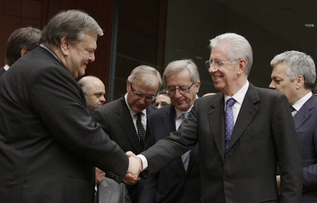 Greek Finance Minister Evangelos Venizelos, left, shakes hands with Italian Prime Minister and Finance Minister Mario Monti during a round table meeting of the eurogroup at the EU Council building in Brussels on Tuesday, Nov. 29, 2011. The 17 finance ministers of countries that use the euro converged on EU headquarters Tuesday in a desperate bid to save their currency and to protect Europe, the United States, Asia and the rest of the global economy from a debt-induced financial tsunami. (AP Photo/Virginia Mayo)