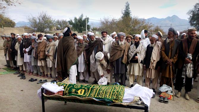 Afghan relatives and villagers prepare to offer funeral prayers over the body of Najia Sediqi, Laghman's head of the women's affairs department in Laghman, east of Kabul, Afghanistan, Monday, Dec. 10, 2012. Gunmen shot and killed the head of the women's affairs department for the eastern Laghman province, said Sarhadi Zewak, a spokesman for the provincial government. (AP Photo/Khalid Khan)