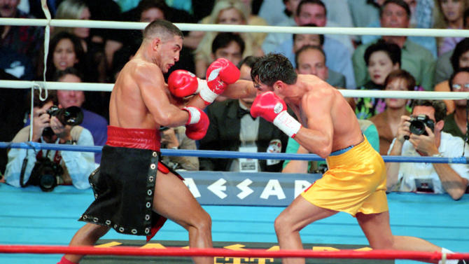 In this Sept. 13, 1997, photo provided by Las Vegas News Bureau, Hector Camacho, left, fights Oscar De La Hoya in a boxing match at Thomas and Mack Center in Las Vegas. Camacho's family tried to decide Wednesday, Nov. 21, 2012, whether he should be removed from life support after a shooting in his Puerto Rican hometown left the former boxing champion clinging to life and his fans mourning the loss of a dynamic and often troubled athlete. (AP Photo/Las Vegas News Bureau, Darrin Bush)