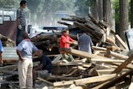 Chinese workers salvage the planks from damaged homes on July 23. The death toll from the worst rains to hit Beijing in more than 60 years has risen to 77 -- more than double the previous figure, according to the Xinhua news agency