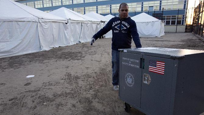 Voting equipment is dragged across dried mud and sand towards tents that have become a make shift voting locations at Scholars' Academy, PS 180, in the Rockaway neighborhood of the borough of Queens, New York, Monday, Nov. 5, 2012. Several normal voting sites have become unusable due to high water and wind damage in the wake of Superstorm Sandy.  (AP Photo/Craig Ruttle)