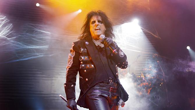 """FILE - This is a Sunday, Oct. 31, 2010 file photo of  U.S musician Alice Cooper as he performs his 'Halloween Night of Fear' show at The Roundhouse in north London.  Shock rocker Alice Cooper gave the audience at Tuesday night's Aug. 14, 2012  """"Rock of Ages"""" show a surprise, by joining the cast of the London  West End musical on stage. The 64-year-old delighted spectators by performing his classic hit """"School's Out"""" - to mark the anniversary of the track going to No. 1 in the U.K. charts 40 years ago this week. (AP Photo/Joel Ryan, File)"""