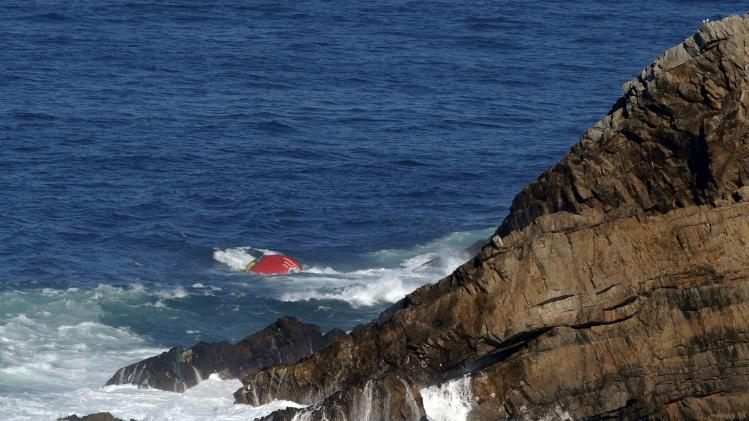 Bow of Portuguese flagged fishing boat Santa Ana hovers above water after it hit a rock and capsized in Cape Penas, northern Spain