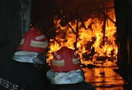 Pakistani fire fighters extinguish the fire at a shoe-making factory in the eastern city of Lahore on Tuesday