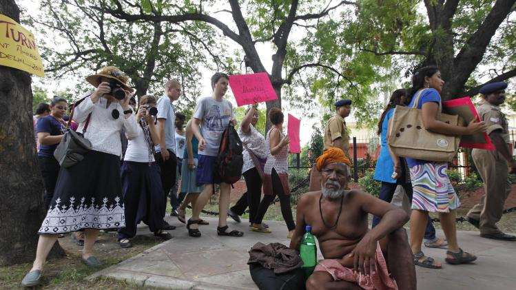 "Supporters of the Delhi ""SlutWalk"" march past a homeless man in New Delhi, India, Sunday, July 31, 2011. There were no short skirts, fishnet stockings or lingerie on display that were the staple of other global ""SlutWalk"" marches as hundreds gathered in India's capital on Sunday to protest sexual violence against women. The event condemned the notion widely held in this traditional society that a woman's appearance can explain or excuse rape and sexual harassment. In India, public sexual taunting or even groping of women, locally known as ""Eve teasing"", is common. (AP Photo/Mustafa Quraishi)"