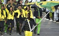 Jamaica's flag bearer Usain Bolt holds the national flag as he leads the contingent in the athletes parade during the opening ceremony of the London 2012 Olympic Games at the Olympic Stadium