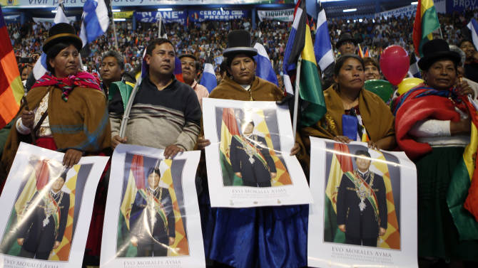 Aymara women hold a posters of Bolivia's President Evo Morales during a welcome ceremony for presidents attending an extraordinary meeting in Cochabamba, Bolivia, Thursday, July 4, 2013. Leaders of Uruguay, Ecuador, Surinam, Argentina and Venezuela are meeting in Bolivia Thursday in support of Morales, who said Thursday that the rerouting of his plane in Europe, over suspicions that National Security Agency leaker Edward Snowden was on board was a plot by the U.S. to intimidate him and other Latin American leaders. (AP Photo/Juan Karita)