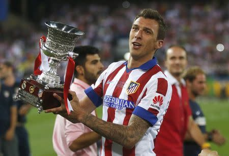 Atletico Madrid's Mario Mandzukic celebrates with the trophy after they won the Spanish Super Cup against Real Madrid at the Vicente Calderon stadium in Madrid