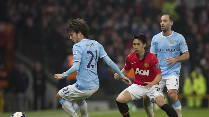 Manchester City's David Silva, left, keeps the ball from Shinji Kagawa, center, as Pablo Zabaleta looks on during their English Premier League soccer match at Old Trafford Stadium, Manchester, England, Tuesday, March 25, 2014