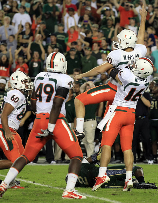 Miami kicker Jake Wieclaw (40) celebrates with teammates, including Chris Ivory (60), Dyron Dye (49) and Spencer Whipple (16) after kicking the game-winning 36-yard field goal during the last seconds