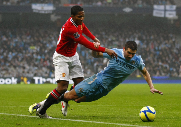 Manchester City's Aleksandar Kolarov, right, vies for the ball against Manchester United's Antonio Valencia during their FA Cup third round soccer match at Etihad Stadium, Manchester, England, Sunday,