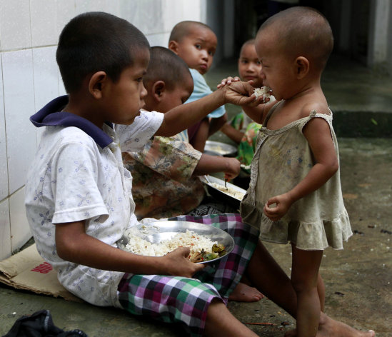 A boy shares food with a young child as they take refuge in a monastery compound in Sittwe, the capital of Rakhine state in western Myanmar, where sectarian violence continues to impact the public, Wednesday, June 13, 2012. Heavy rain Wednesday brought an uneasy calm to western Myanmar after five days of deadly sectarian strife, though residents said they were too afraid to sleep at night and faced food shortages. (AP Photo/Khin Maung Win)