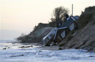 Collapsed houses lie on the beach after a storm surge in Hemsby, eastern England December 6, 2013. REUTERS/Darren Staples