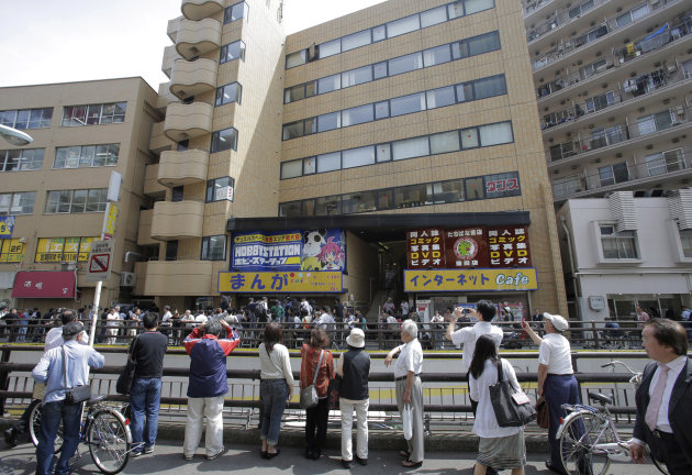 People look at a comic book cafe, center in background, where Katsuya Takahashi, a former Aum Shinrikyo cult member, was detained by police, in Tokyo Friday, July 15, 2012. Police arrested Takahashi,