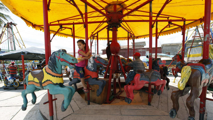 In this picture taken on April 21, 2012, a young girl rides on a carousel of a street fair near the harbor in the seaside town of Gibara, Cuba. (AP Photo/Kathy Willens)