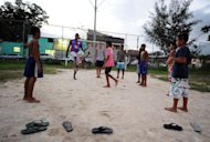 Brazilian football player Anderson Basilio (2-R) plays with children in a street of Campo Grande, 70 km from Rio de Janeiro, on January 23, 2013. In this soccer-mad nation of 194 million people, which will host the 2014 World Cup, &quot;the beautiful game&quot; is a ticket out of poverty for millions of poor youths