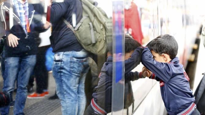 Migrants disembark from train at railway station in Vienna