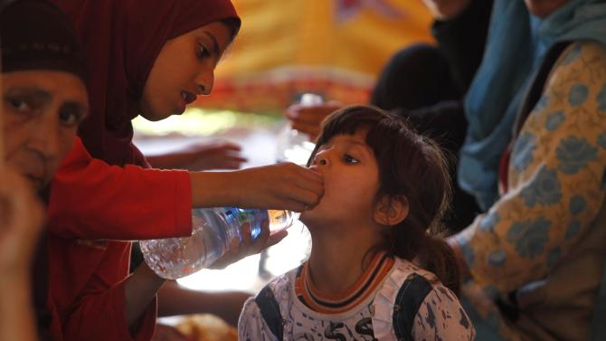 Children displaced by floods eat their meals at a relief camp in Srinagar