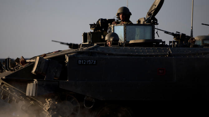 "Israeli soldiers ride on top of an armored personal carrier close to the Israel Gaza Border, southern Israel, Thursday, Nov. 15, 2012. Israel's prime minister says the army is prepared for a ""significant widening"" of its operation in the Gaza Strip. Benjamin Netanyahu told reporters on Thursday that Israel has ""made it clear"" it won't tolerate continued rocket fire on its civilians. (AP Photo/Ariel Schalit)"