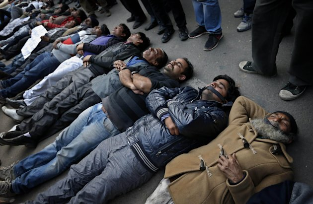 Indian men and women lie down on the ground mimicking dead bodies as they mourn the death of a gang rape victim in New Delhi, India, Saturday, Dec. 29, 2012. Shocked Indians on Saturday were mourning