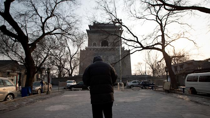 In this photo taken on Dec. 26, 2012, a Chinese man walks on the square near the historical Drum and Bell Tower, seen in the background, in Beijing.  In a corner of old Beijing, behind two well-known landmarks, the sun may soon set for the last time on dozens of scuffed courtyard homes in a plan to recreate a piece of the country's glorious dynastic past.(AP Photo/Andy Wong)