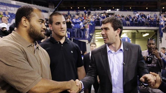Indianapolis Colts quarterback Andrew Luck, who was the first pick in the NFL football draft, meets with defensive tackle Fili Moala, left, and tackle Anthony Castonzo as he arrives for a draft party at Lucas Oil Stadium after he was introduced by the team in Indianapolis, Friday, April 27, 2012. (AP Photo/Michael Conroy)