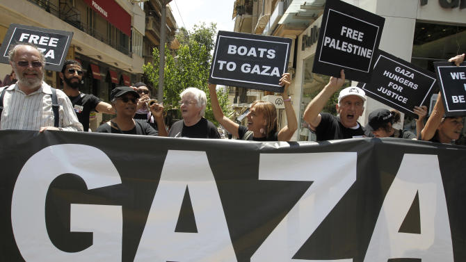 U.S. activists chant slogans as they hold placards after a news conference about an international flotilla to blockaded Gaza, in Athens, Monday, June 27, 2011. Organizers say Israel is pressuring Greece to halt the ships' departure. (AP Photo/Petros Giannakouris)