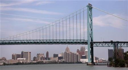 The Detroit city skyline is seen behind the Ambassador Bridge, an international border-crossing linking Windsor, Ontario with Detroit, along the Detroit River in Detroit, Michigan July 21, 2012. REUTERS/Rebecca Cook