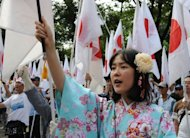 A right-wing activist raises a Japanese flag during an anti-China rally in Tokyo