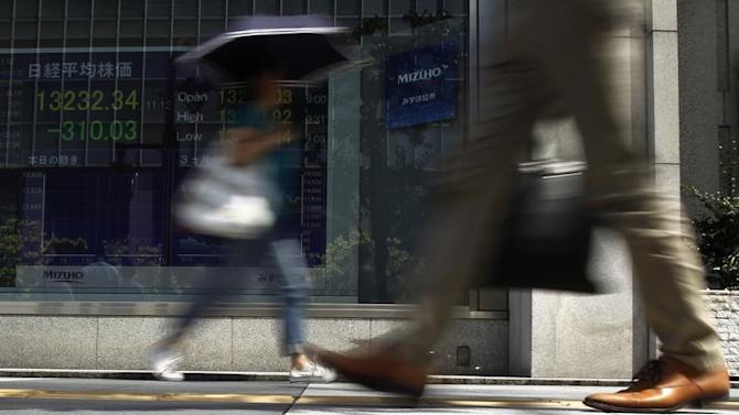 Pedestrians walk past a stock quotation board displaying Japan's Nikkei share average outside a brokerage in Tokyo