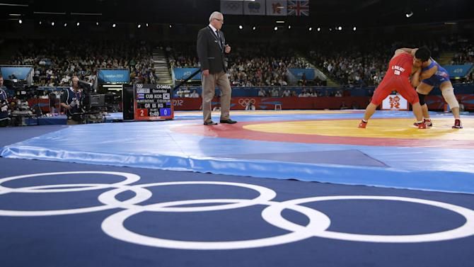 FILE - The Aug. 5, 2012 file photo shows Cuba's Gustavo Balart, left, competing with South Korea's Choi Gyu-jin during 55-kg Greco-Roman wrestling competition at the 2012 Summer Olympics in London. IOC leaders have dropped wrestling for the 2020 Games in a surprise decision to scrap one of the oldest sports on the Olympic program. The IOC executive board decided Tuesday, Feb. 12, 1013 to retain modern pentathlon — the event considered most at risk — and remove wrestling instead from its list of core sports.  (AP Photo/Paul Sancya, file)